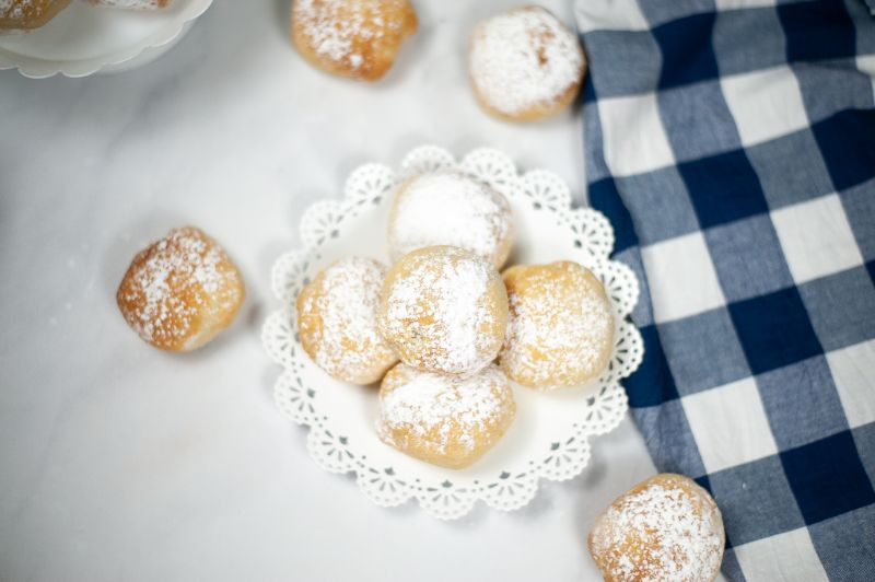 overhead view of deep fried oreos on a white doily and on a white cloth next to a blue and white checkered cloth