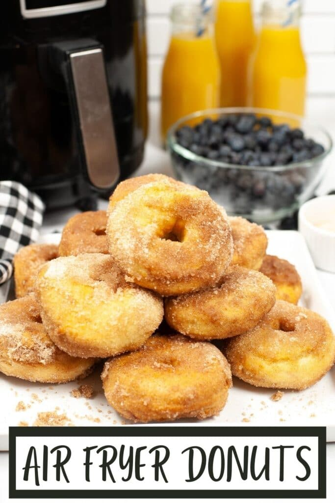 Plate of cinnamon sugar air fryer biscuit donuts in front of bowl of blueberries, glasses of orange juice and an air fryer with title text reading Air Fryer Donuts
