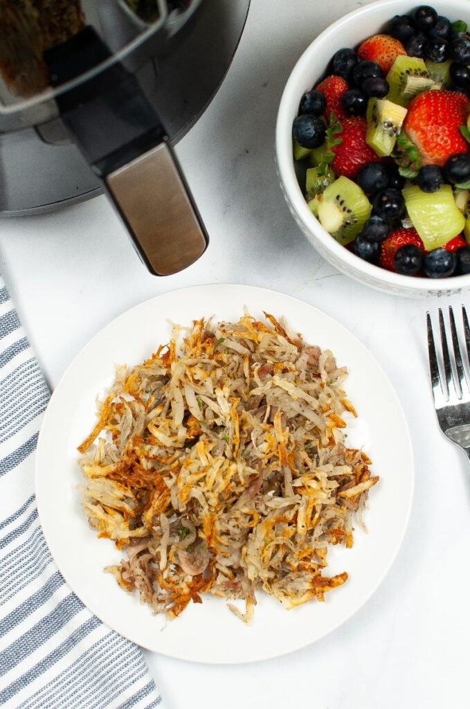overhead view of hash browns on a white plate on a white table next to a fork, a bowl of fruit, and and air fryer
