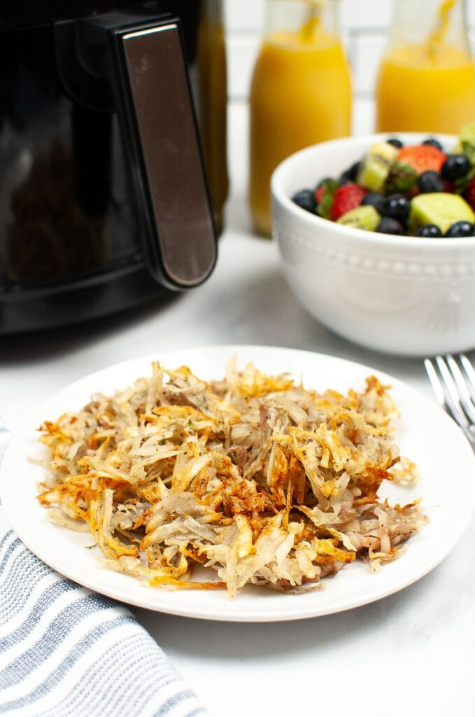 hash browns on a white plate on a white table next to a fork, a bowl of fruit, 2 glasses of orange juice and and air fryer