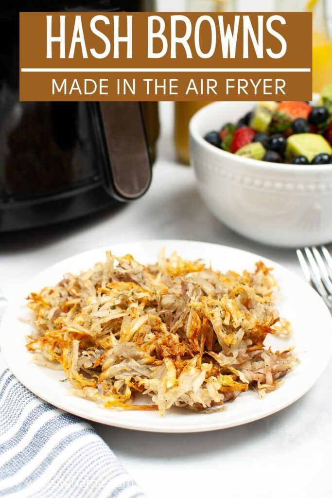 hash browns on a white plate on a white table next to a fork, a bowl of fruit, 2 glasses of orange juice and and air fryer with title text reading Hash Browns Made In The Air Fryer