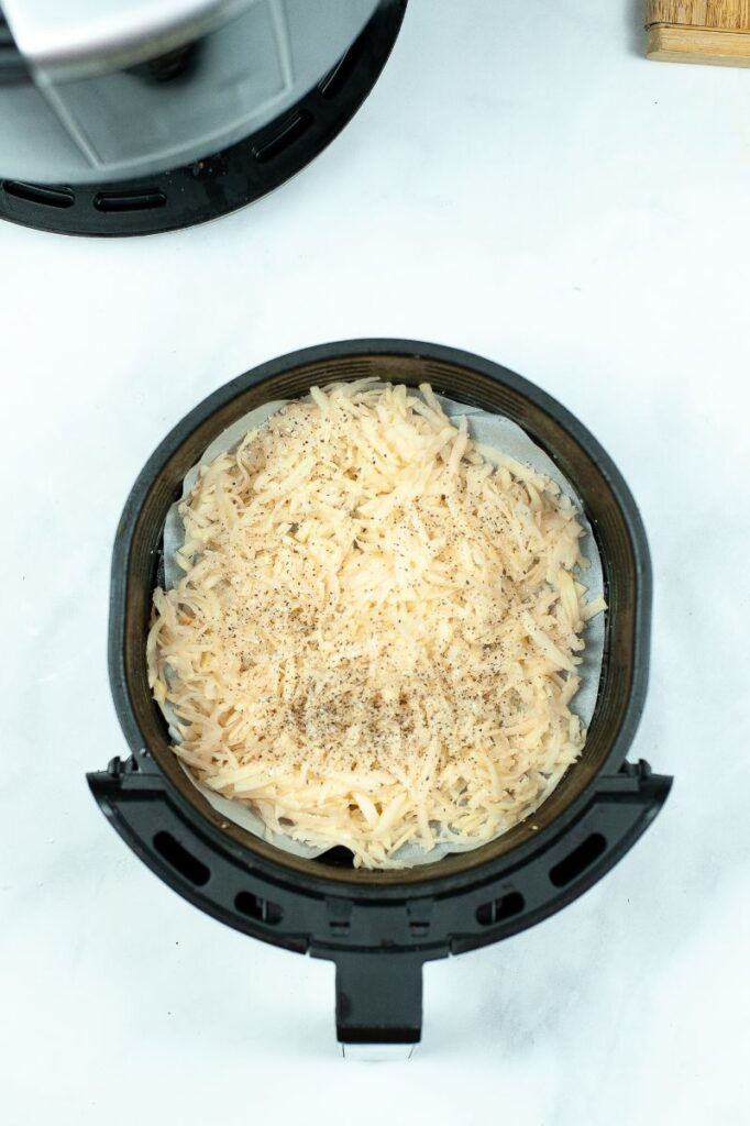 seasoned shredded potatoes in an air fryer on a white table