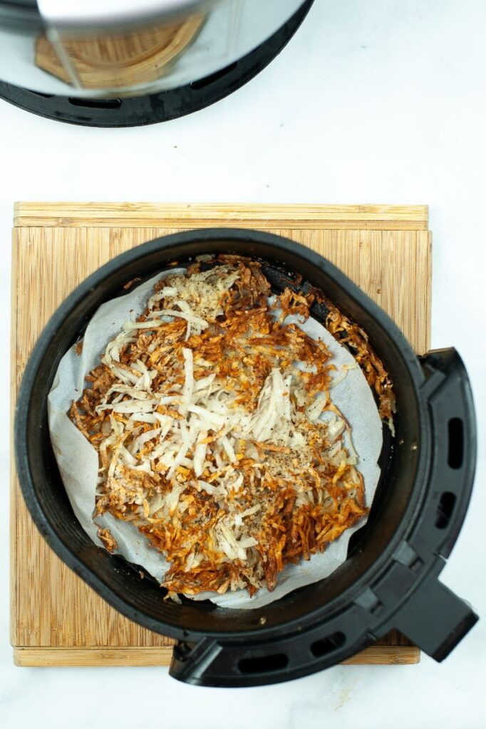 hash browns in an air fryer on a wooden cutting board