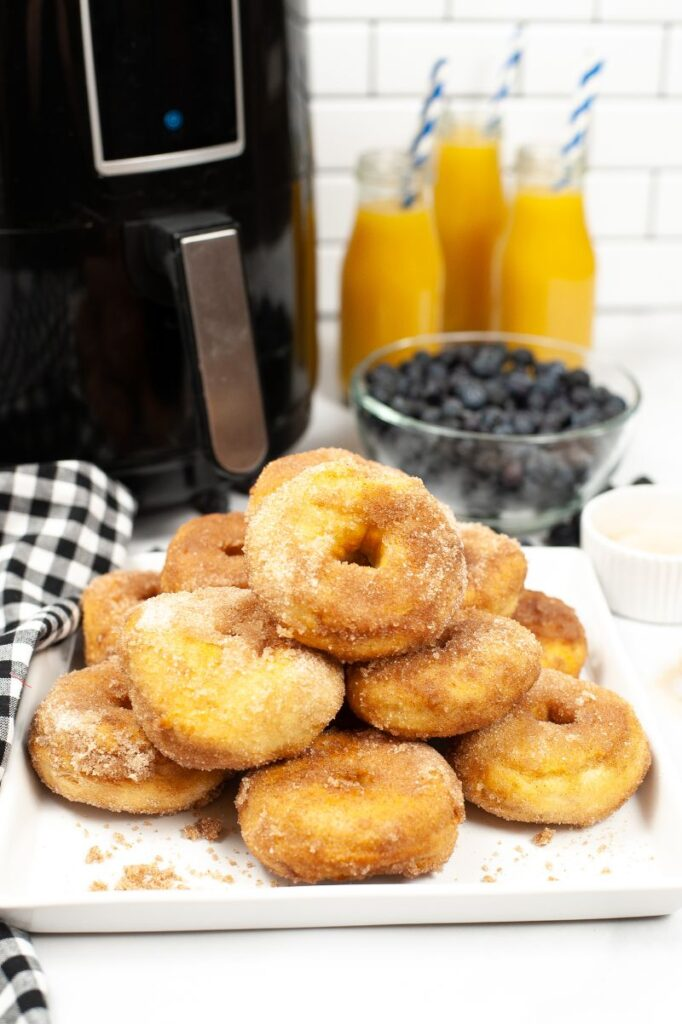 Plate of cinnamon sugar air fryer biscuit donuts in front of bowl of blueberries, glasses of orange juice and an air fryer