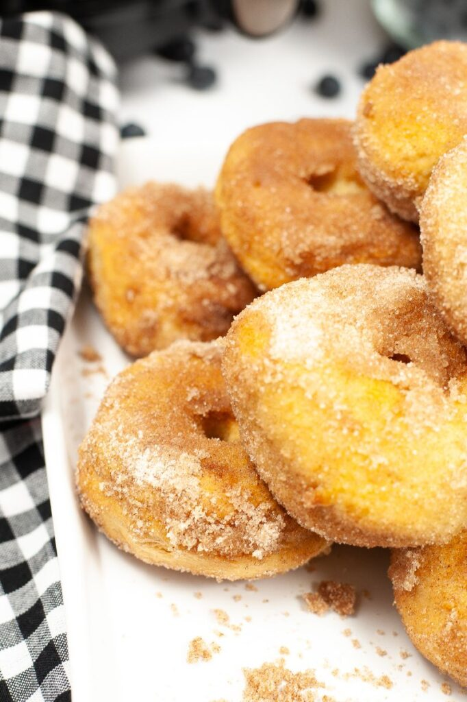 close up of a plate of cinnamon sugar air fryer biscuit donuts in front of bowl of blueberries, glasses of orange juice and an air fryer