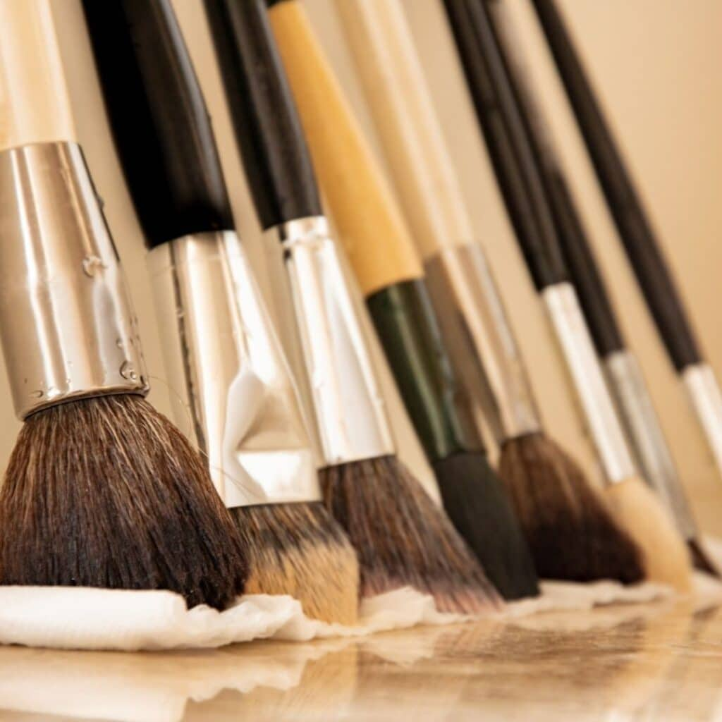 close up of makeup brushes on a paper towel on a counter