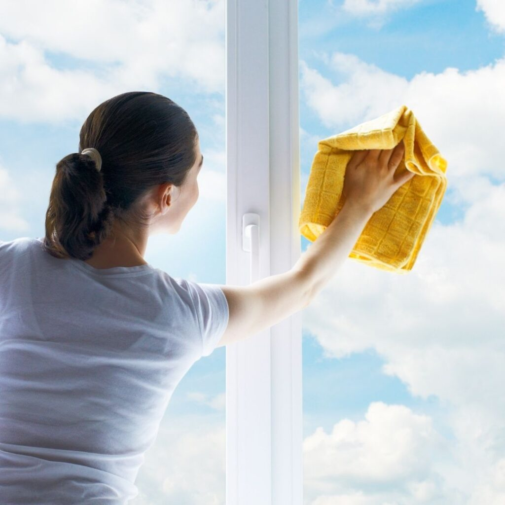 a lady using a yellow cloth to clean windows with clouds in the blue sky seen outside the windows