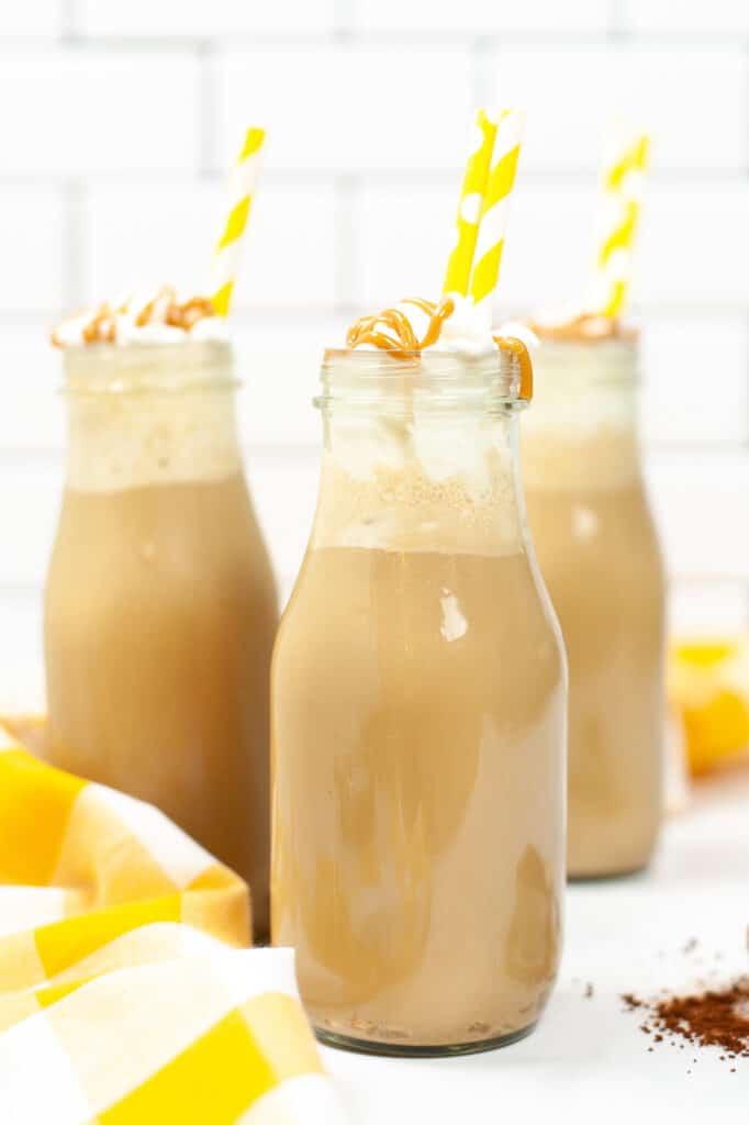 Copycat Starbucks Iced Caramel Macchiato in three jars with yellow straws