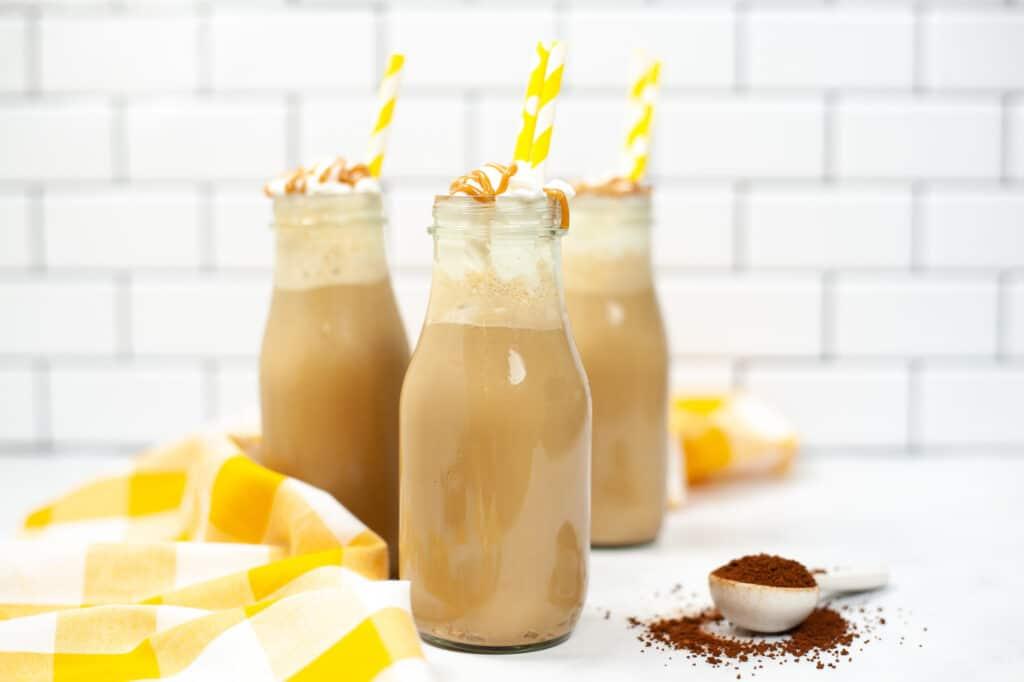 3 Copycat Starbucks Iced Caramel Macchiato in glasses on counter