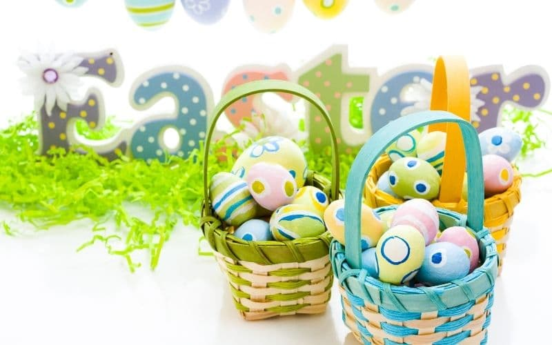 decorated Easter eggs in three colorful baskets with a colorful Easter sign on fake grass in the background