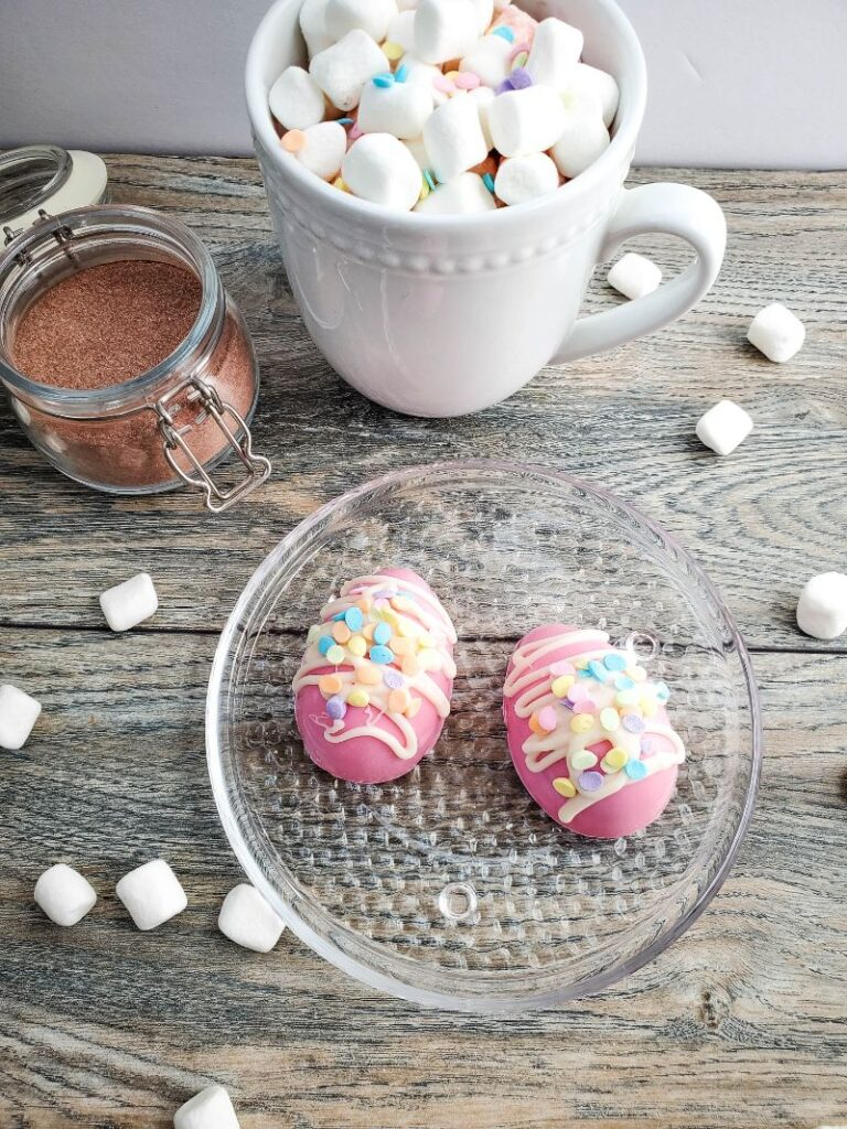 two Easter egg hot cocoa bombs on a glass plate surrounded by marshmallows on a wood table next to a white cup of hot chocolate and cocoa in an open glass jar