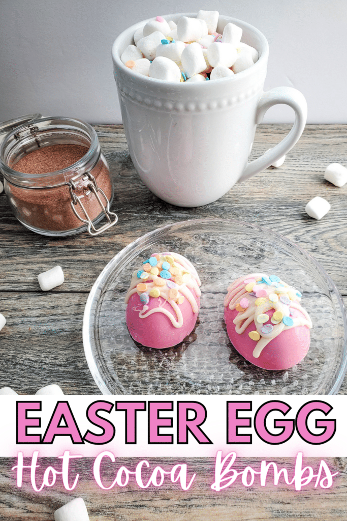 two Easter egg hot cocoa bombs on a glass plate surrounded by marshmallows on a wood table next to a white cup of hot chocolate and cocoa in an open glass jar with title text reading Easter Egg Hot Cocoa Bombs