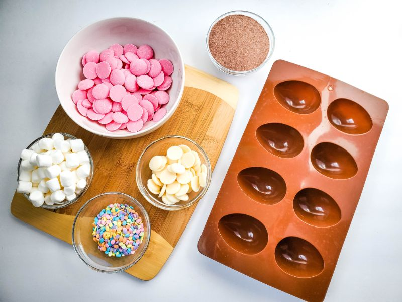 ingredients in bowls needed to make Easter egg hot cocoa bombs and an egg shaped mold