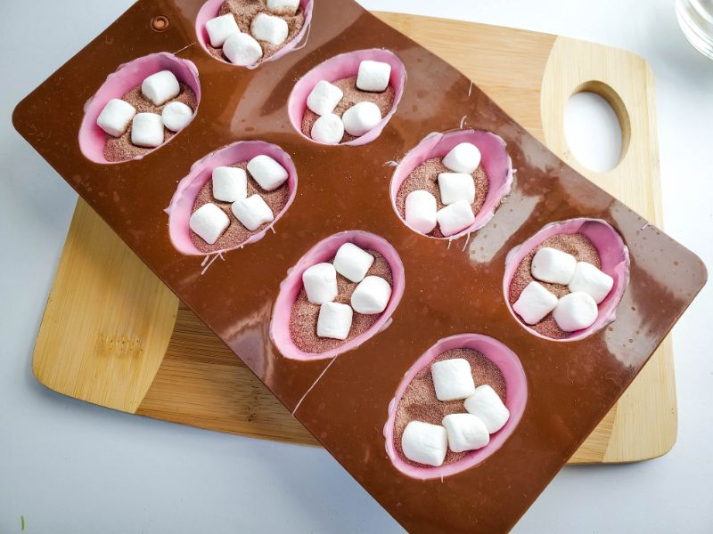 an egg mold coated with melted pink candy filled with cocoa powder and marshmallows