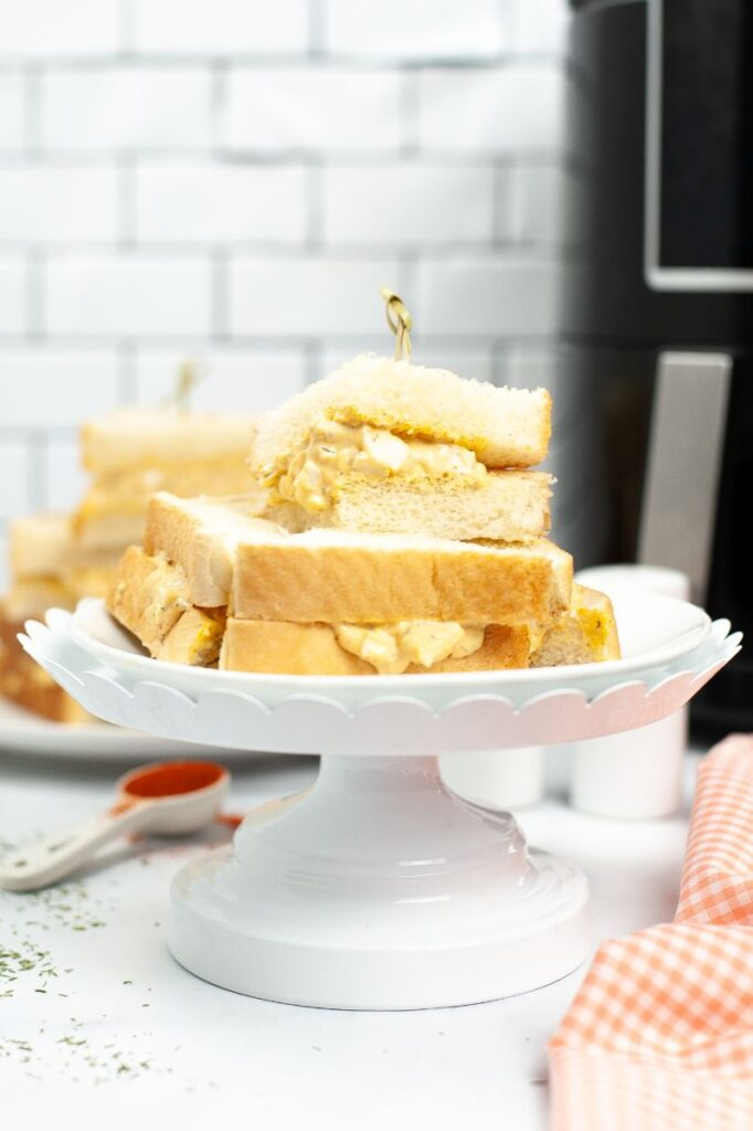 cut up egg salad sandwich stacked on a white cake stand next to an orange and white checkered cloth on a white table with more sandwiches and an air fryer in the background