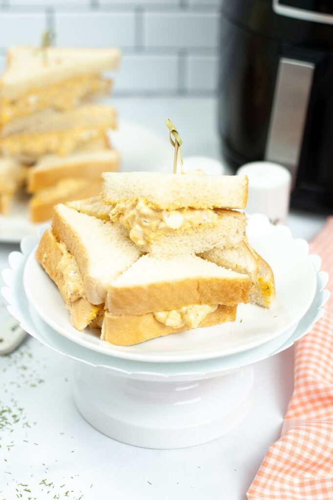 cut up egg salad sandwich stacked on a white cake stand next to an orange and white checkered cloth on a white table with more sandwiches in the background