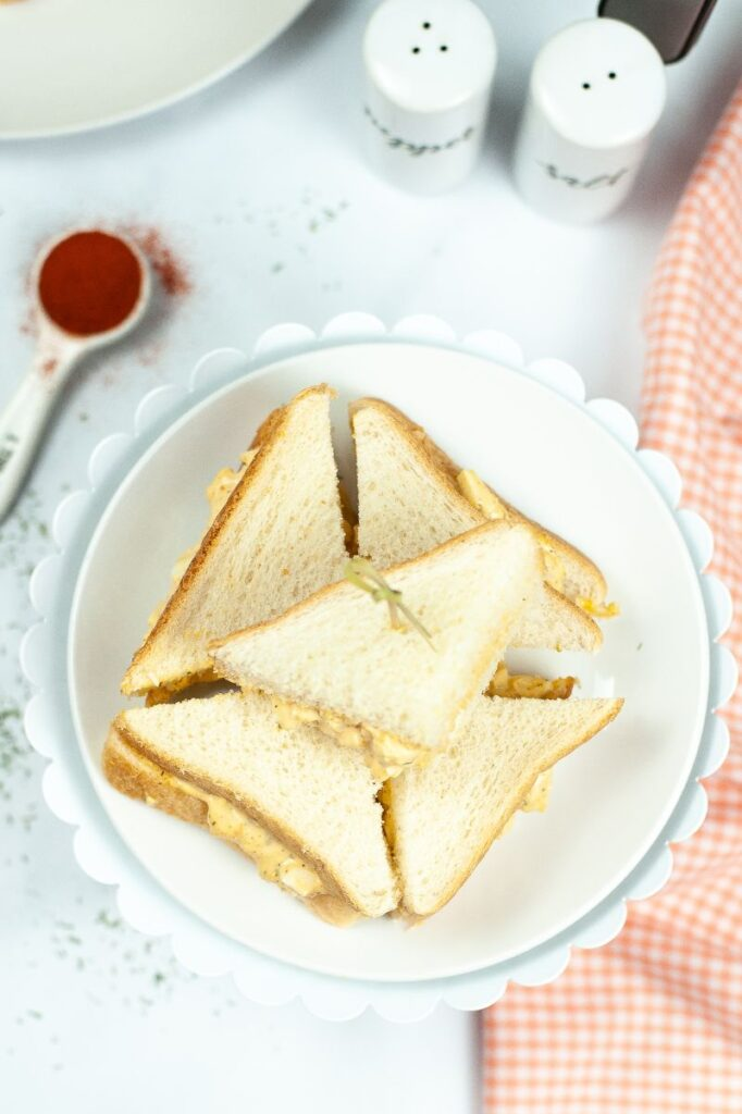 overhead view of cut up egg salad sandwich stacked on a white cake stand next to an orange and white checkered cloth, tablespoon of a spice and salt and pepper shakers on a white table