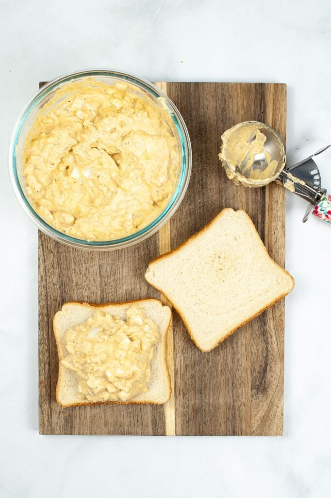 egg salad in a glass bowl next to egg salad on bread, another slice of bread and a cookie scoop all on a wooden board