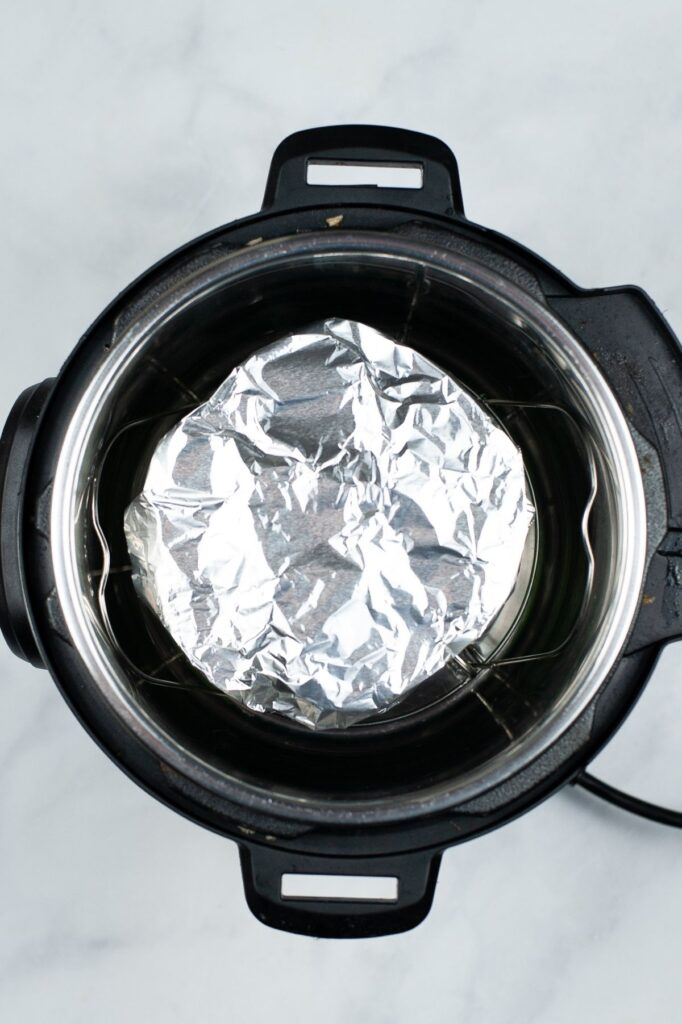 a foil wrapped mold on a trivet in an instant pot