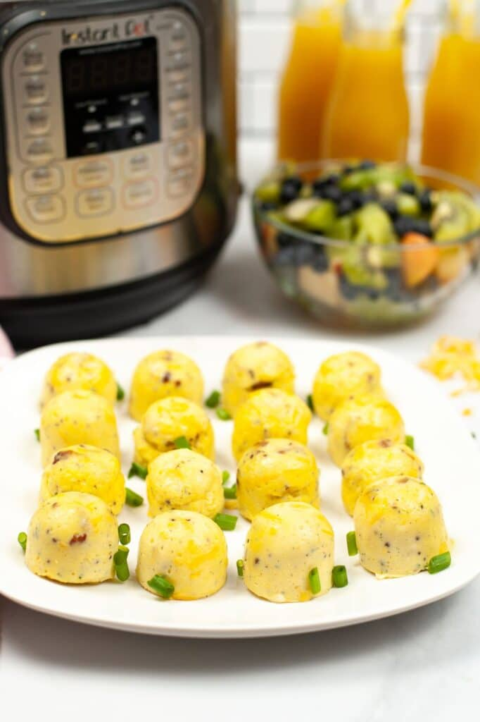 egg bites on a white plate  with an instant pot, fruit, and glasses of orange juice in the background