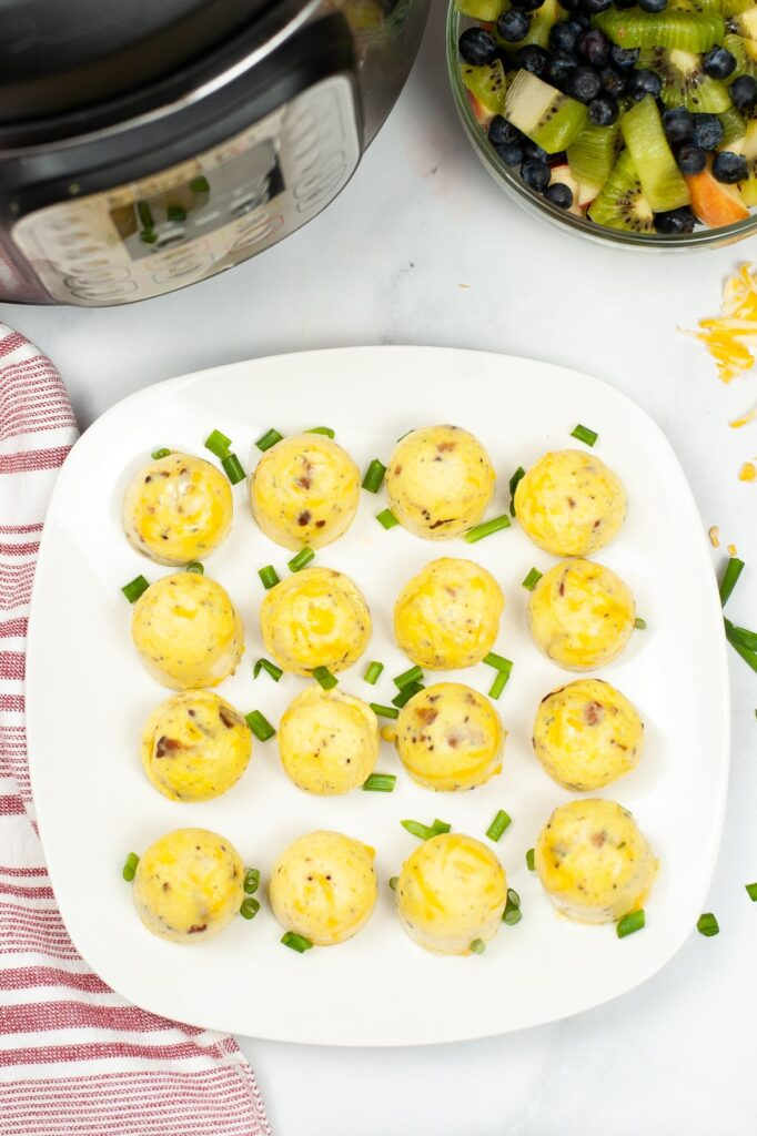 overhead view of egg bites on a white plate  with an instant pot, fruit, and glasses of orange juice in the background