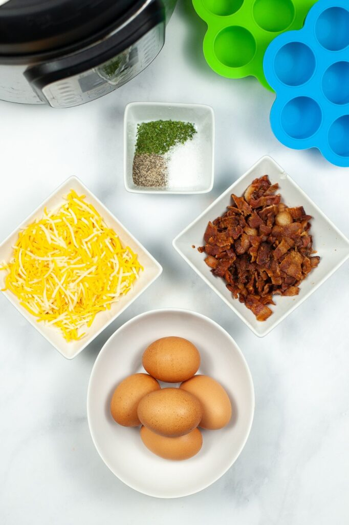 ingredients needed to make egg bites n white bowls, egg molds and an instant pot