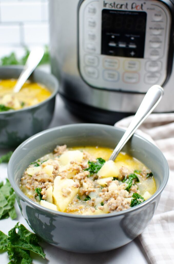 Instant Pot Zuppa Toscana soup in two bowls with spoons in them with an instant pot in the background