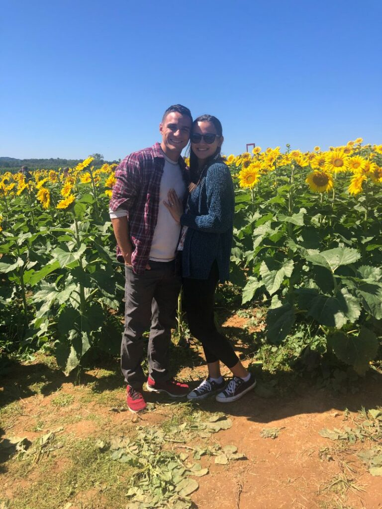 a young man and lady standing in a sunflower field
