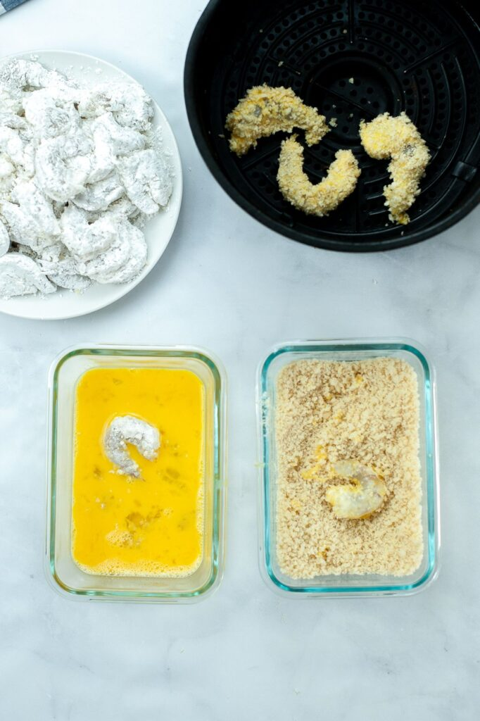 shrimp being dipped in egg, panko crumbs and cornstarch, and placed in an air fryer