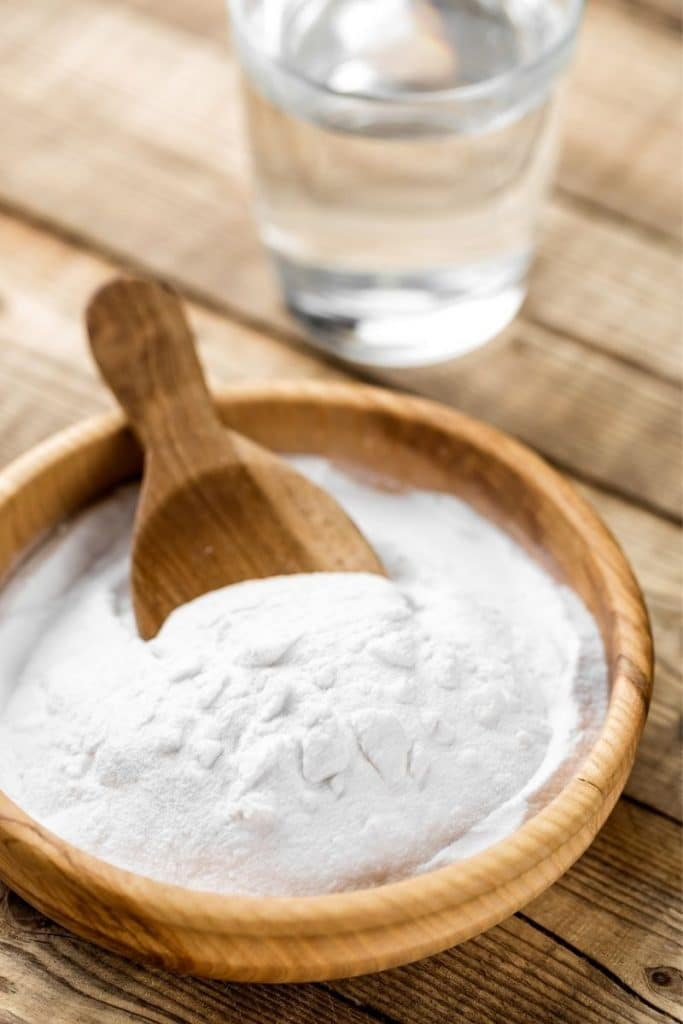 a wooden spoon and baking soda in a wooden bowl on a wood table