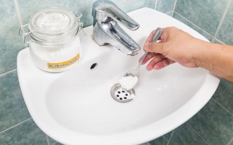 a hand putting a spoon of baking soda down a bathroom sink drain