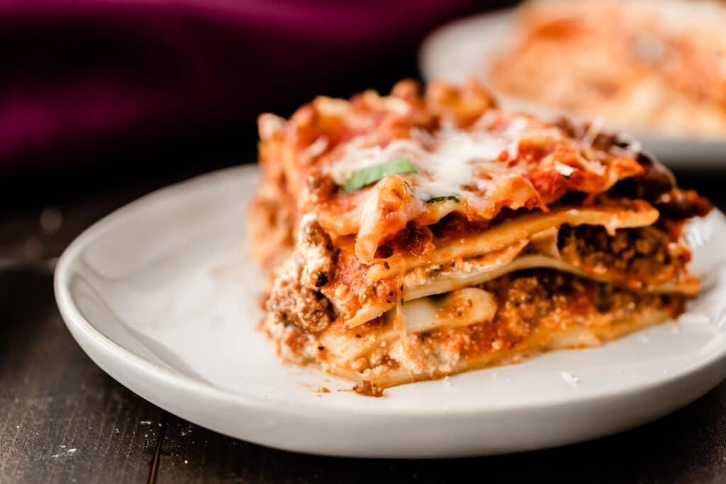 piece of lasagna on white round plate