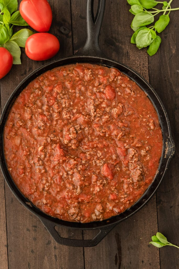 ground beef and tomato in cast iron skillet