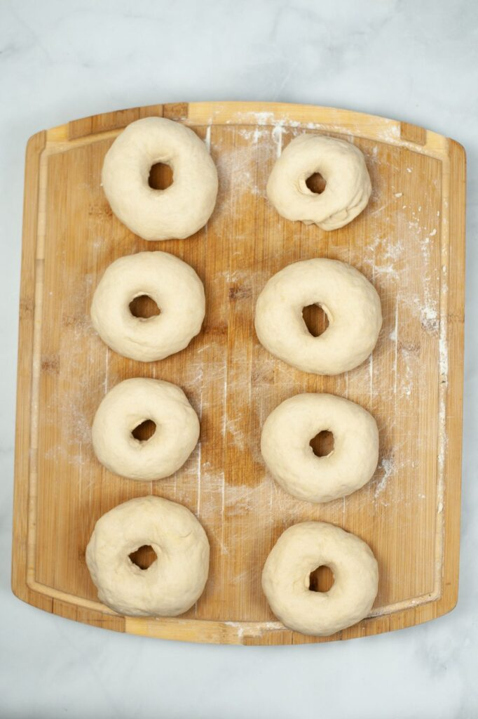 8 raw bagels on a wooden cutting board
