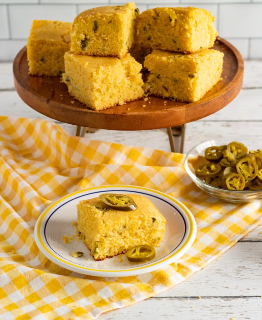 a piece of jalapeno cornbread topped with jalapenos on a white plate on a yellow and white checkered cloth with more cornbread and jalapenos in the background