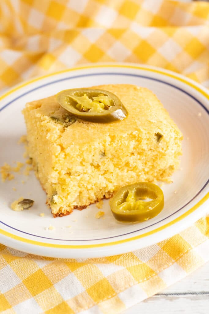 a piece of jalapeno cornbread topped with jalapenos on a white plate on a yellow and white checkered cloth