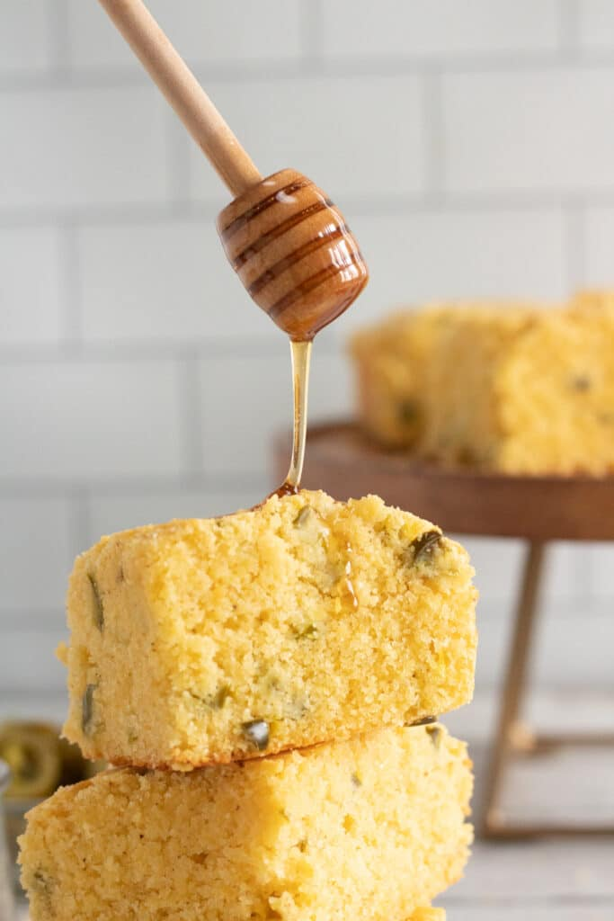 jalapeno cornbread being drizzled with honey