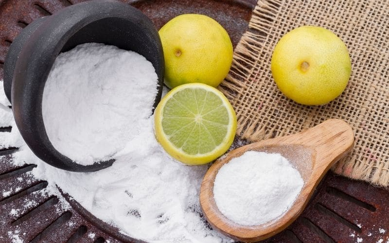 baking soda spilling out of a bowl and on a wooden spoon next to some lemons