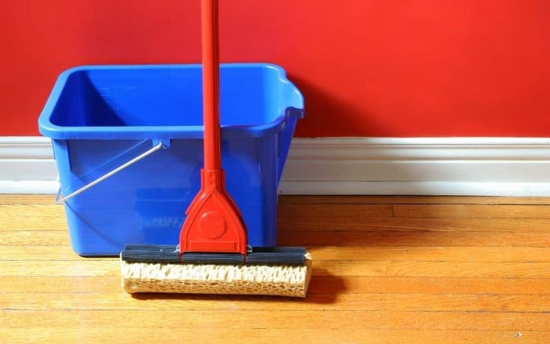a mop and bucket on a wood floor leaning against a red wall