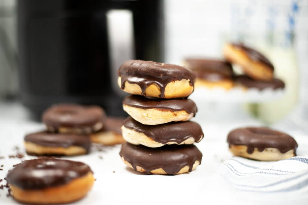 stack of glazed chocolate donuts with an air fryer in the background