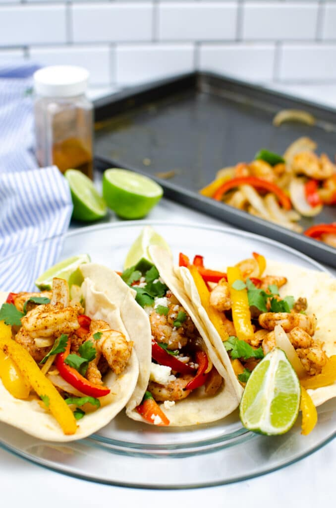 Shrimp Sheet Pan Fajitas on a glass plate with lime, with another lime, the sheet pan, and a blue and white striped cloth in the background