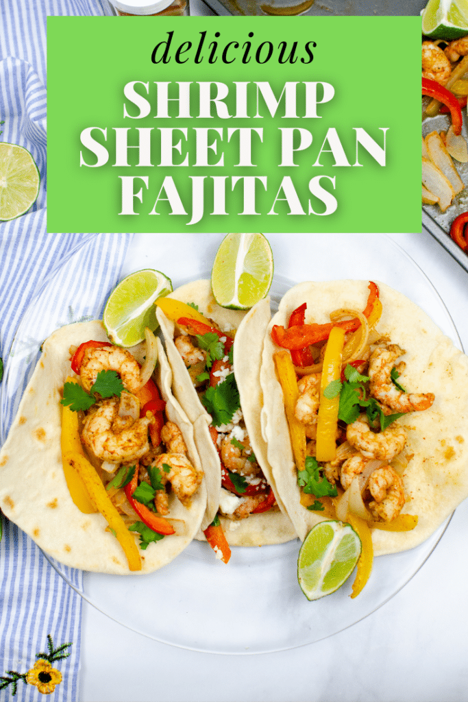 Shrimp Sheet Pan Fajitas on a glass plate with lime, with another lime, the sheet pan, and a blue and white striped cloth in the background with title text overlay reading delicious Shrimp Sheet Pan Fajitas