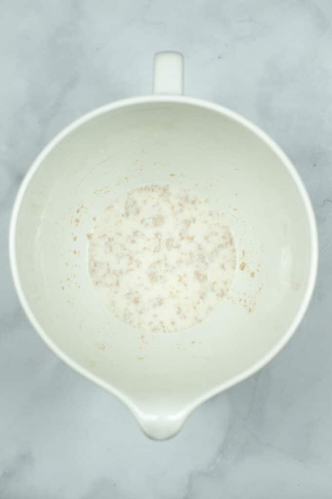letting the milk, yeast and sugar foam in a white bowl