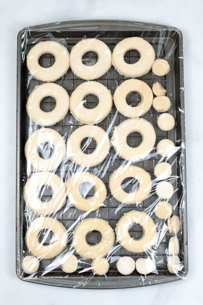 donuts on a baking sheet wrapped in plastic to let them raise
