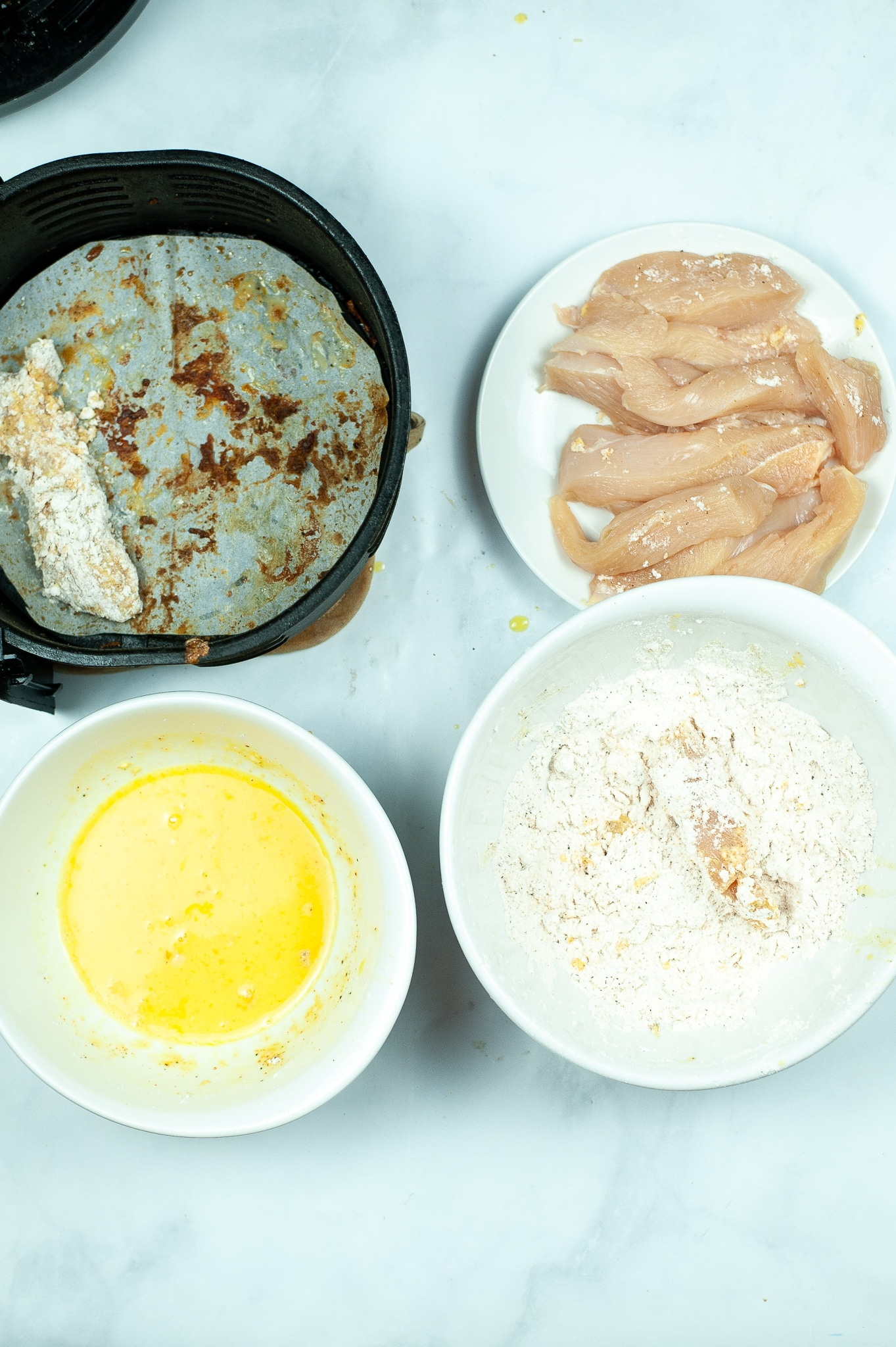 cut up raw chicken breasts, a bowl of flour, a bowl of egg, a coated chicken breast slice in the air fryer