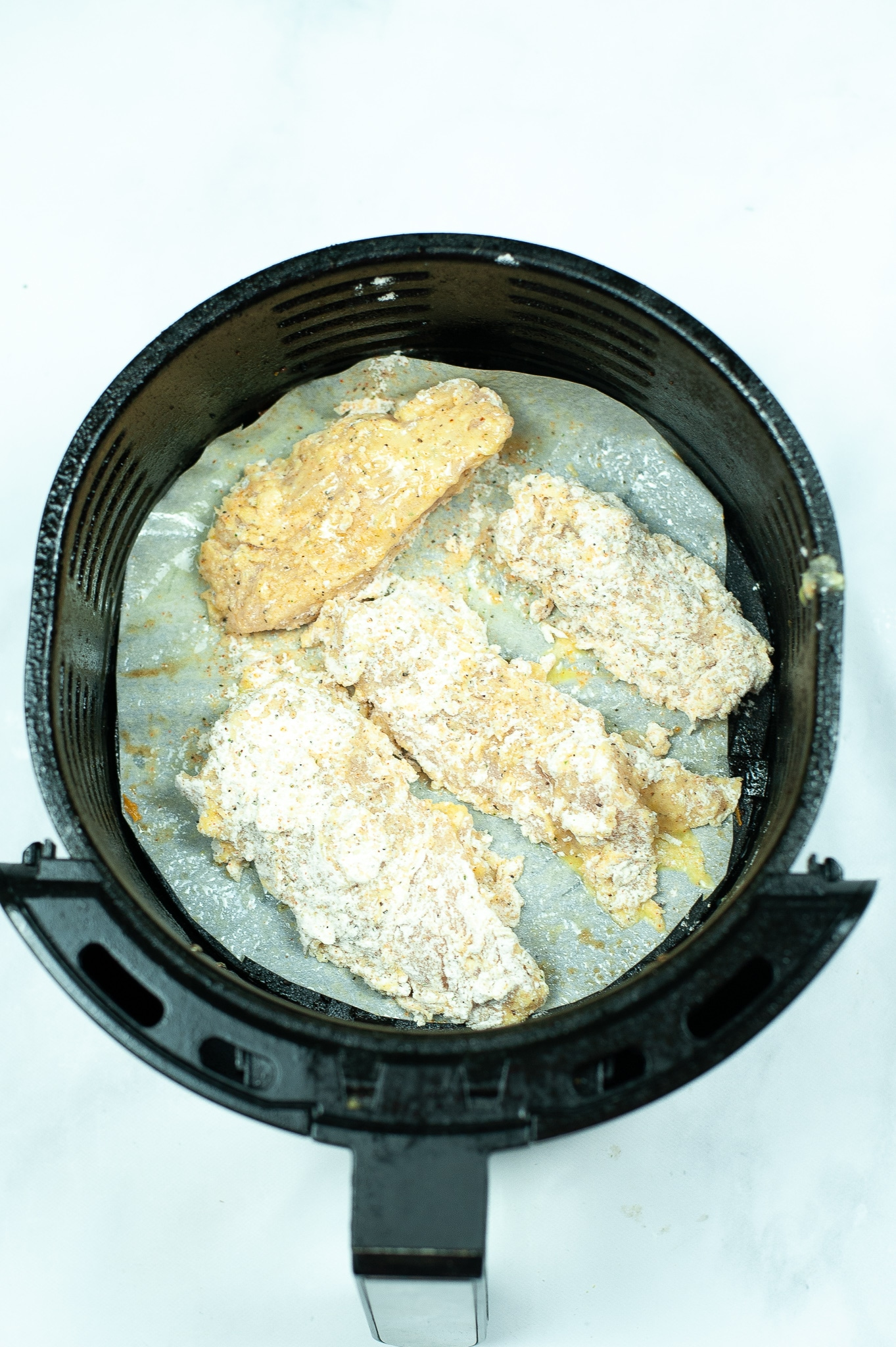 coated chicken breast strips being cooked in an air fryer