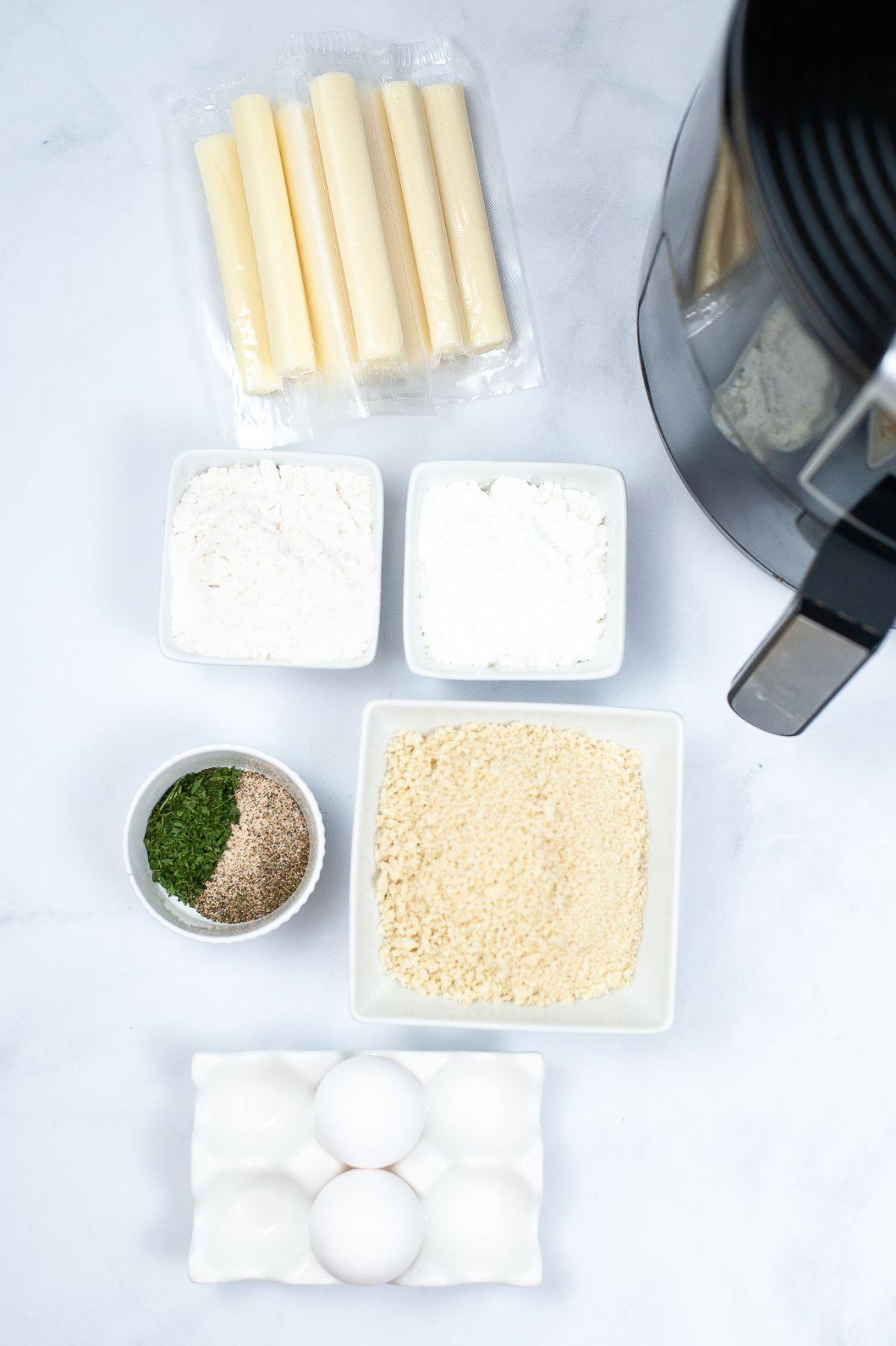 Air Fryer Mozzarella Sticks ingredients in small bowls, mozzarella cheese sticks, cornstarch, flour, panko, and eggs.