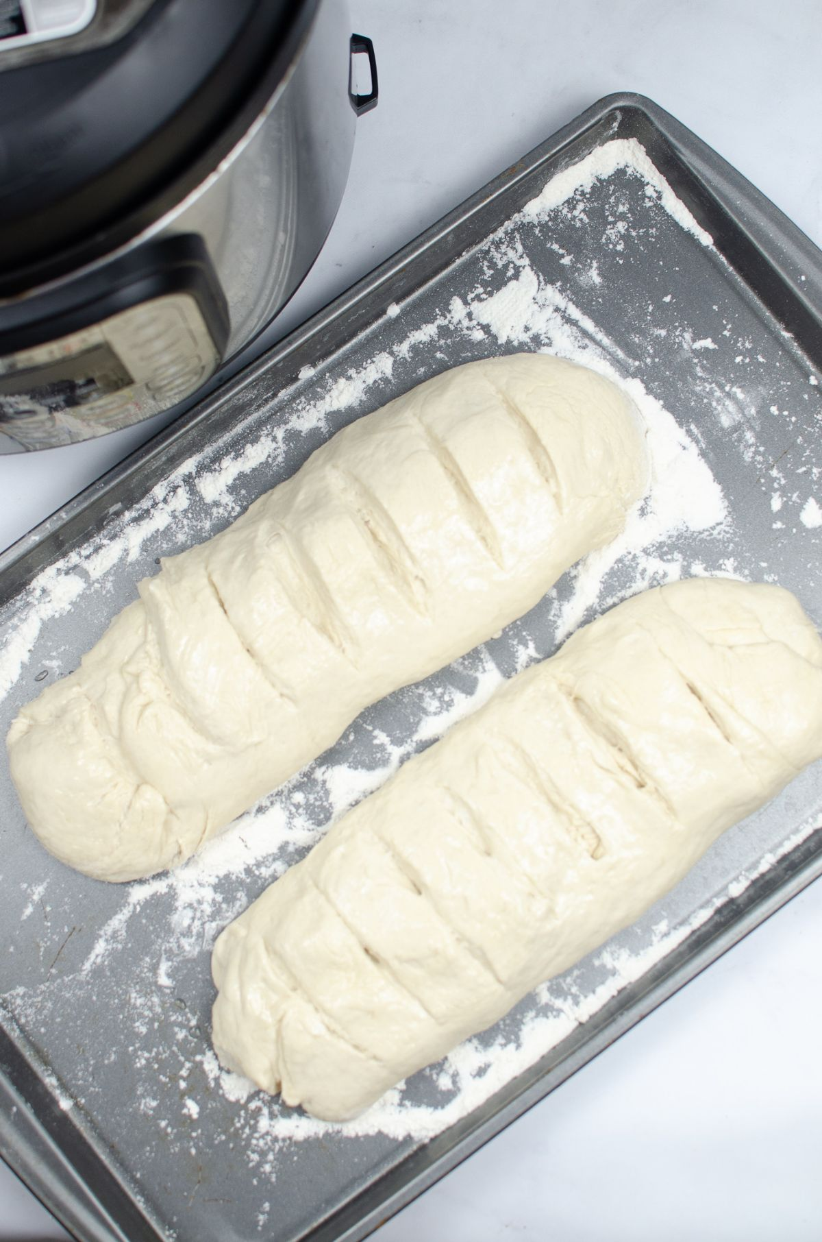 Dough formed in the shape of a long loaf with the top part scored with a knife.