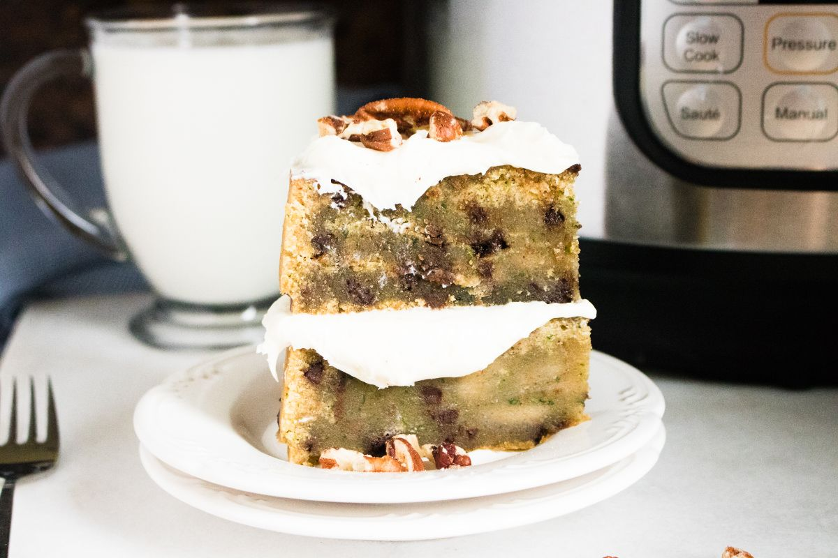 A slice of the Zucchini bread on a pile of two serving plate with a glass of milk and the instant pot in the background and a fork beside it.