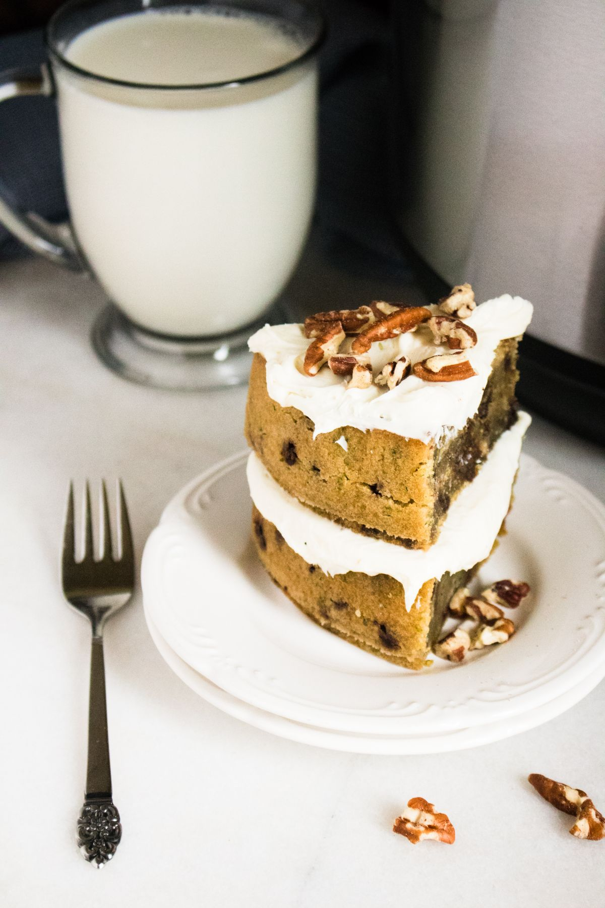 A slice of the Zucchini bread on a serving plate with a glass of milk in the background and a fork beside it.